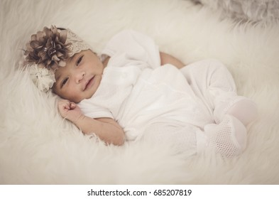 portrait of cute and adorable newborn baby with  head band on furry mat.motherhood and parenting concept.