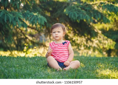 Portrait of cute adorable pensive serious little  Caucasian baby girl toddler in park outside. Happy lifestyle childhood concept. Child kid sitting on grass during summer sunset