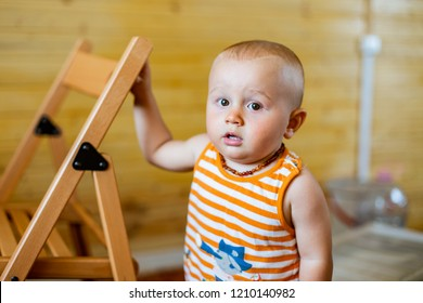 A portrait of a cute adorable serious baby boy of 12 months or 1 year old looking at the camera wearing amber teething baby necklace in a sleeveless striped orange top holding the back of the chair.