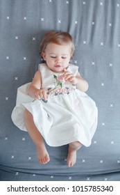 Portrait of cute adorable smiling Caucasian blonde baby girl one year old in white dress lying with rose flowers on grey bed sheet in bedroom, view from top above. Happy childhood lifestyle