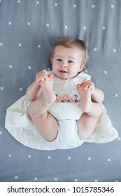 Portrait of cute adorable smiling Caucasian blonde baby girl one year old in white dress lying on grey bed sheet in bedroom, view from top above. Happy childhood lifestyle concept