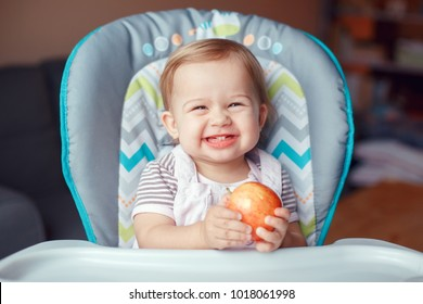 Portrait of cute adorable smiling laughing Caucasian child kid girl sitting in high chair eating apple fruit. Everyday lifestyle. Real authentic sweet home moment