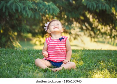 Portrait of cute adorable smiling little  Caucasian baby girl toddler in park outside. Happy lifestyle childhood concept. Laughing joyful kid child sitting on grass and looking up during summer sunset