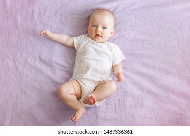 Portrait of cute adorable smiling white Caucasian baby girl boy with blue eyes four months old lying on bed looking at camera. View from top above. Happy childhood lifestyle.