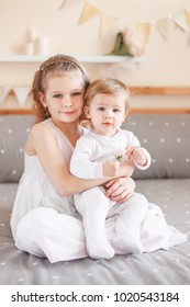 Portrait of cute adorable white Caucasian girl holding little sister baby on laps knees. Smiling children sitting together on bed in bedroom looking in camera. Sibling love