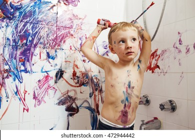 Portrait of cute adorable white Caucasian little boy playing and painting with paints  on wall in bathroom having fun, lifestyle childhood concept