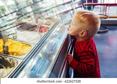 Portrait of cute adorable white Caucasian funny blond child boy looking at ice cream in shop window, trying to choose one, looking surprised puzzled, emotional face expression