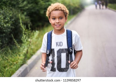 Portrait of the cute african american boy who is going to school with his school  backpack. Student mixed boy on his way to the school. Study for children. Road. Shooting on the july 2018.