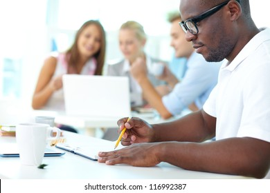 Portrait of cute African guy working with his partners on background