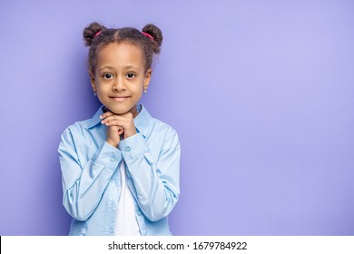 portrait of cute african kid girl isolated over purple background. beautiful shy little girl posing at camera, smile