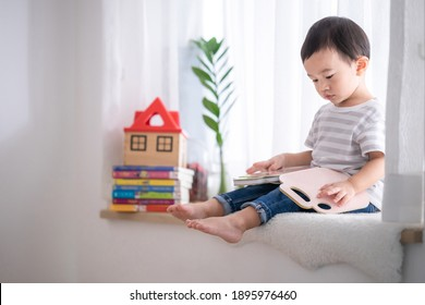 Portrait cute Asian baby boy reading a book,Baby early education,Child development concept.