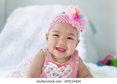 Portrait of cute asian baby in pink dress on carpet wool,happy baby concept,smile,thail little baby