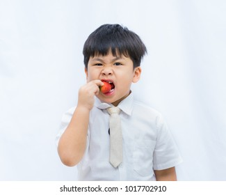 Portrait cute Asian boy eating red strawberry on white background,
