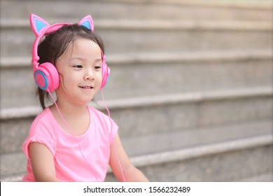 Portrait Cute Asian girl 3 year old feeling absolutely delighted . Asia kid wear cat earphone, She sit on stairs and smile and enjoy to listen music. concept Happiness is all around. Kid and Music.
