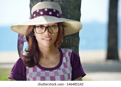 Portrait of a cute Asian girl in a hat on a background of the sea