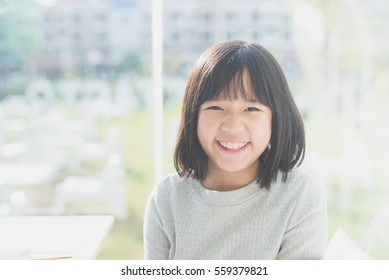 Portrait of Cute Asian girl sitting in a restaurant under sunlight