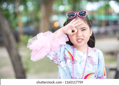 Portrait of cute asian girl smiling and doing Dele Alli Challenge.