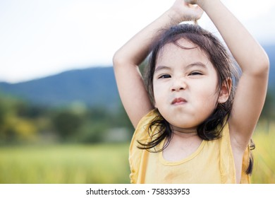 Portrait of cute asian little child girl, funny and angry face.