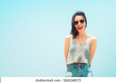 Portrait of a cute asian teenager young woman stand against blue sky and cloud background. wearing sunglasses. wind blows her hair. filtered image to vintage tone. light effect added. hipster concept