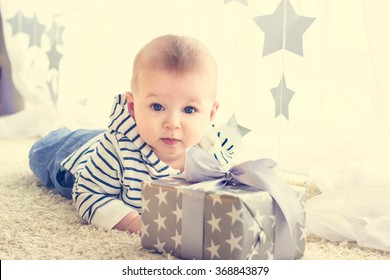 Portrait of a cute baby boy with big blue eyes wearing jeans and striped hoodie sweater lying in front of his present in wrapped box with ribbon. Birthday, Mother's day or Christmas presents concept