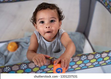 Portrait of cute baby boy in cot holding a toy block, childhood development educational