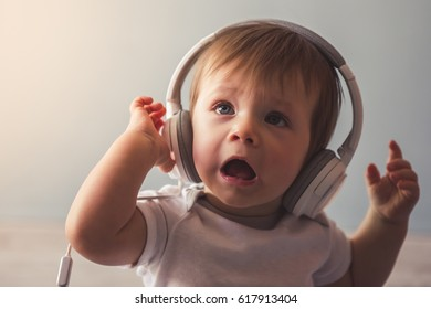 Portrait of cute baby boy with headphones saying something