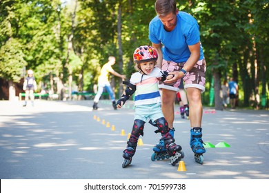 Portrait of cute baby boy with inline skating instructor in the park learning to skate.