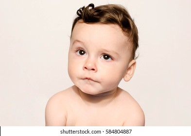 Portrait of a cute baby boy looking up cringing making a funny face lifting his eyebrow wondering. Adorable naked child making cute mimic.