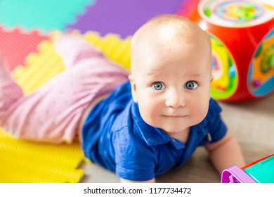 Portrait of cute baby boy lying on floor covered with multicolored soft mats in playroom. Adorable toddler kid smiling and playing with colorful toys indoor. Chilld growing and development