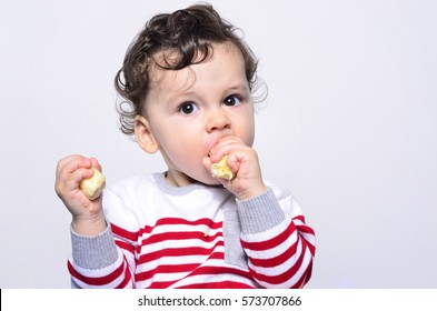 Portrait of a cute baby eating a banana. One year old kid eating fruits by himself. Adorable curly hair boy being hungry.
