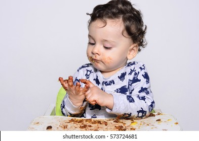 Portrait of a cute baby eating cake making a mess. One year old kid eating a slice of birthday smash cake by himself getting dirty. Adorable curly hair boy being hungry.