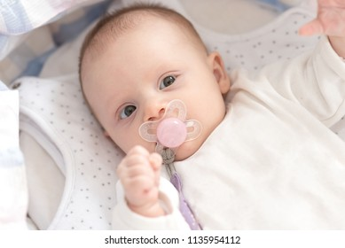 Portrait of cute baby girl with pacifier lying in her crib