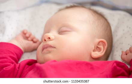Portrait of cute baby girl sleeping in her crib, close up