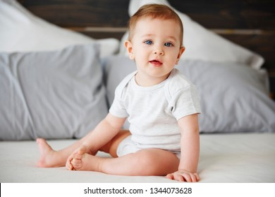Portrait of cute baby sitting on bed