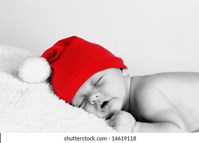 A portrait of a cute baby wearing a santa hat, black and white with color restored in hat
