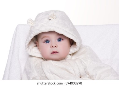 portrait of a cute baby in white hood bear. baby with big blue eyes sitting on a chair and looking into the camera