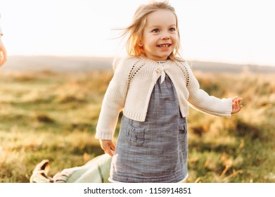 Portrait of a cute beatiful and happy girl running through the sunny field