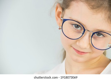 portrait of a cute and beautiful 8 year old girl with glasses