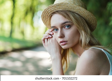 Portrait of a cute beautiful blonde in a straw hat close-up