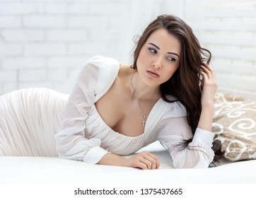The portrait of cute beautiful brunette woman lying on a bed in bedroom.