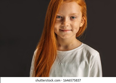 portrait of cute beautiful caucasian little girl with long red hair looking at camera and smile. children with natural hair isolated over black background