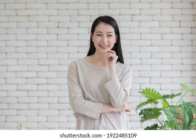 Portrait of cute beautiful mix race Asian adult woman folded arms pose to camera with self-confident and friendly manner
