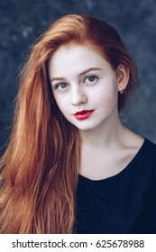 Portrait of cute beautiful young girl with freckles and red hair close-up. Sensitive red lips.