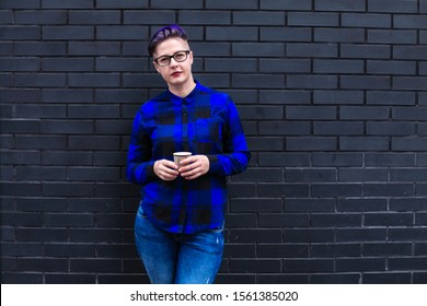 Portrait of cute beautiful young lesbian with short haircut and trendy boyish clothes drinking cup of coffee, friendly.
