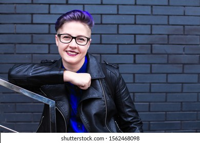 Portrait of cute beautiful young lesbian with short haircut and trendy boyish clothes