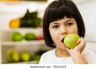 Portrait of cute black hair little girl eating green apple