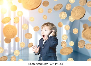 Portrait of a cute blond baby boy talking on a smartphone and being surprised. He is standing in an office lobby under a bitcoin rain.