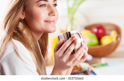 Portrait of cute blond female having coffee in the kitchen, enjoying happy lazy morning, peace and relaxation at home