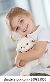 Portrait of cute blond little girl hugging teddy