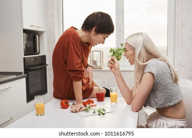 Portrait of cute blonde girl holding salary and talking to her girlfriend while she sits on kitchen table and laughs outloud. Two girls decided tos tart diet together but all they both want is burger